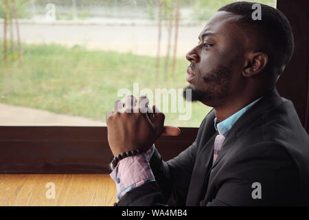Afro american pensive tired young businessman is sitting in cafe. Portrait of young black man looks at window turns his head and looks at camera. Bearded young guy wears shirt and suit jacket. - Stock Photo