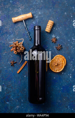 Bottle of red wine with a corkscrew and ingredients for making mulled wine on a dark blue background. Winter drink concept - Stock Photo