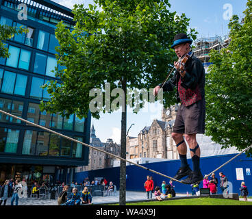 Edinburgh, Scotland, UK, 17 August 2019. Edinburgh Festival Fringe: A Fringe street performer on Middle Meadow Walk outside the Quartermile playing a violin while walking on a tightrope - Stock Photo