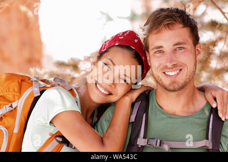 Happy young hikers backpacking on summer travel. Portrait of two friends teenagers or student couple wearing rucksacks bags smiling hiking during road trip vacation or doing volunteering. - Stock Photo