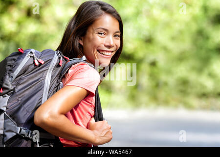 Happy young Asian Chinese backpack girl student. Cute adult woman backpacker smiling at camera with school bag doing summer backpacking travel in nature.