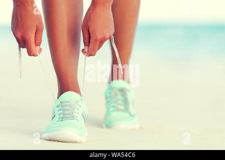 Healthy runner woman tying running shoes laces getting ready for beach jogging. Closeup of hands lacing cross training sneakers trainers for cardio workout. Female athlete living a fit and active life - Stock Photo