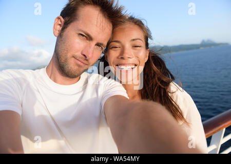 Selfie couple taking holiday self-portrait picture of themselves. Happy multiracial friends having fun together on cruise vacation in Caribbean destination taking smartphone photos as summer memories. - Stock Photo