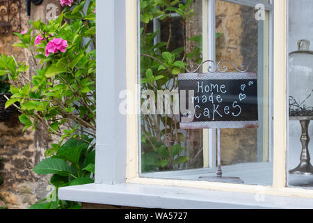 Home made cakes sign in the window of Smiths of Bourton Tea rooms. Bourton on the water. Cotswolds. Gloucestershire, England - Stock Photo