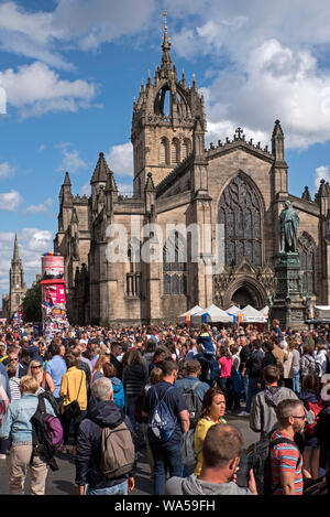 A busy Royal Mile by St Giles Cathedral in Edinburgh during the Edinburgh Fringe Festival. - Stock Photo