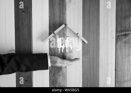 Grayscale image of male hand in a suit under a paper cut silhouette of a family under a roof of wooden pegs in a conceptual image. Over stripped backg - Stock Photo