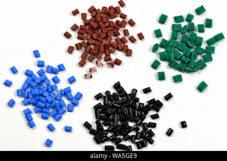 blue, brown, black, and green heaps of polymer resin for injection moulding in laboratory - Stock Photo