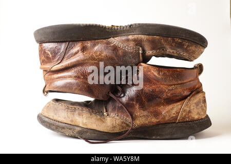 Dirty pair of old leather boots on white background - Stock Photo