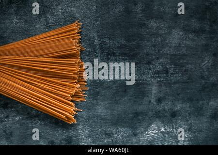 raw wholegrain spaghetti in a bun on a dark background. View from above. - Stock Photo