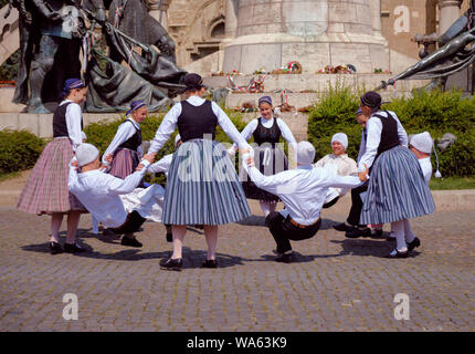 Hungarian Traditional dance troop in folkloric customs with a public performance in square. Dance in circle with man doing crunching dance. - Stock Photo