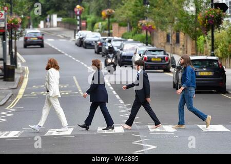 Abbey Road, London, UK.  18th August 2019. Four Beatles impersonators dressed as John Lennon, Ringo Star, Paul McCartney and George Harrison crossing the zebra crossing on Abbey Road in London, UK.  The zebra crossing is outside the famous Abbey Road Studio's and was made famous by The Beatles Abbey Road album.  Picture Credit: Graham Hunt/Alamy Live News - Stock Photo