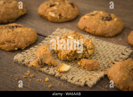 cookies, oats, mixed nuts and raisins on a wooden table;  selective focus. - Stock Photo