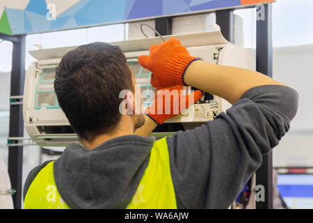 Worker mounts and connects the air conditioner on the wall of the house - Stock Photo