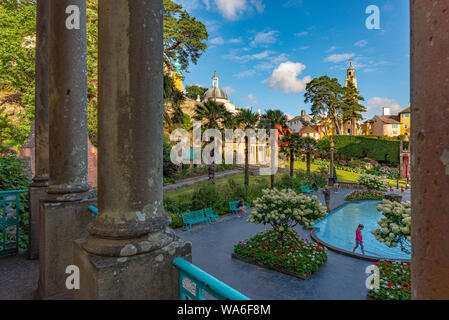 Penrhyndeudraeth, Wales, UK - Aug 15, 2019: Portmeirion main square with people around the formal pond, taken from a balcony - Stock Photo