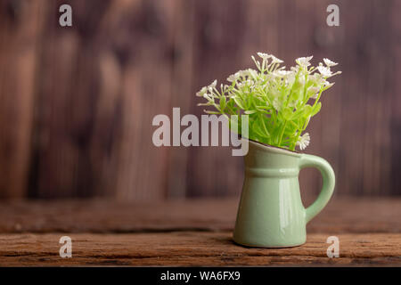 Plastic flowers in a green jug ceramic tile place on the old wooden table with blurred backgrounds and copy space for text. - Stock Photo