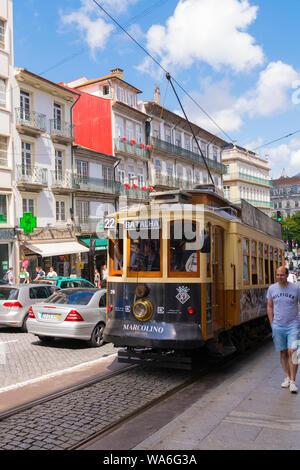Portugal Oporto Porto Rua dos Clérigos street scene old tram streetcar rails lines cars traffic sidewalk pavement houses balconies shops stores - Stock Photo