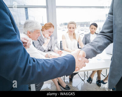 Handshake of business partners after discussion of the financial reports, their team on background - Stock Photo