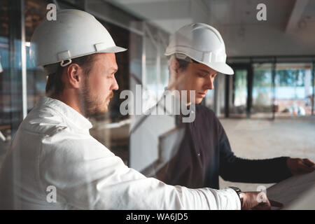 Worker and engineer have meeting while look drawing building under constuction. Two building engineers wearing safety hard hat discussing blueprint on - Stock Photo