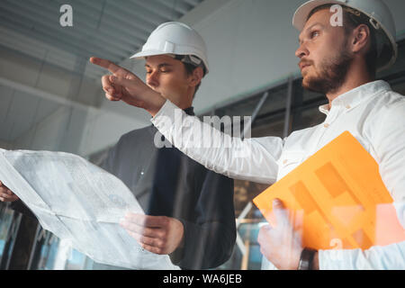 Builder worker and safety inspector wearing helment have meeting while look on construction blueprint. Two engineers building under constuction - Stock Photo