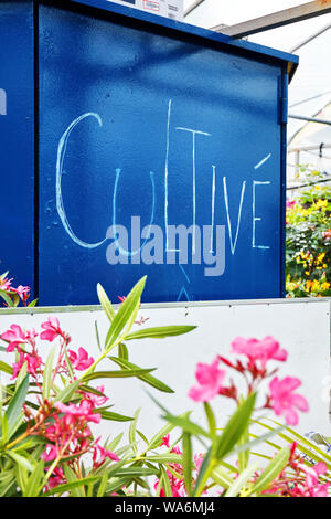 The word cultivate written in French in a flower market greeenhouse - Stock Photo