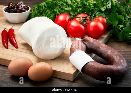Turkish bryndza sheep milk cheese on wooden table with wooden cutting board with fermented sausage, eggs, olive, parsley and tomatoes. - Stock Photo