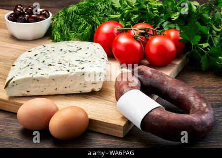 Turkish Van milk cheese with herbs on wooden table with wooden cutting board with fermented sausage, eggs, olive, parsley and tomatoes. - Stock Photo
