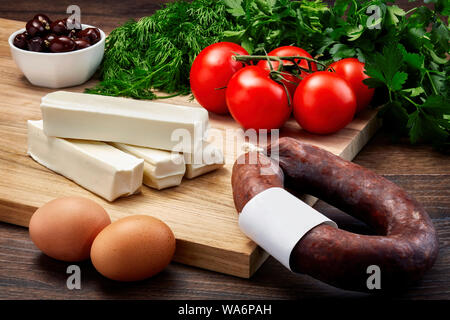 Turkish string cheese on wooden table with wooden cutting board with fermented sausage, eggs, olive, parsley and tomatoes. - Stock Photo