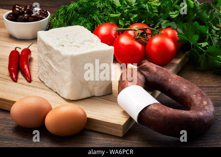 Turkish fresh white cheese on wooden table with wooden cutting board with fermented sausage, eggs, olive, parsley and tomatoes. Turkish breakfast. - Stock Photo