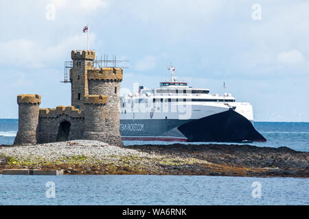 After a run from Liverpool, high-speed ferry Manannan passes the Refuge Tower on St Mary's Isle at the entrance to Douglas Harbour on the Isle of Man. - Stock Photo