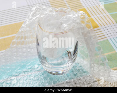 Thick bottom glass half packaged with transparent bubble wrap on a checkered tablecloth. Material for packing fragile items for safe transportation.