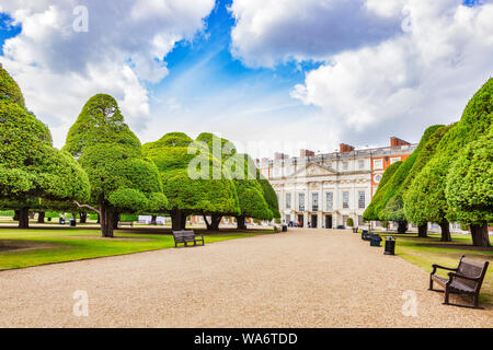 9 June 2019: Hampton Court, Richmond UK - The East Front of the palace, seen beyond an avenue of yew trees in the Great Fountain Garden, with a group - Stock Photo