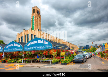 Exterior view of Atwater Market building and its clock tower with flower shops around in Montreal, Quebec, Canada. - Stock Photo