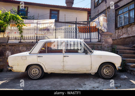 Vintage scrap Fiat 124 car parked in front of a shanty house in the ghetto of Hamamonu district, Ankara, Turkey. - Stock Photo