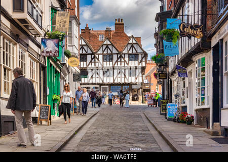 2 July 2019: Lincoln, UK - Tourists sightseeing in Steep Hill, the city's famous medieval street. The half timbered, black and white building at the t - Stock Photo