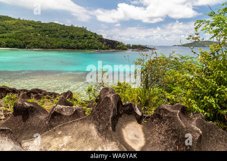 Panoramic view at the landscape on Seychelles island Mahé with turguoise water, mountains  and granite rocks - Stock Photo