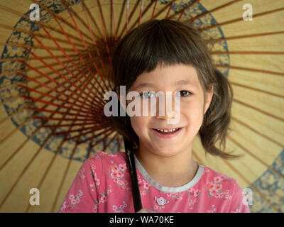 Cute mixed-race little girl (Caucasian and Southeast Asian) smiles under her traditional Chinese oil-paper parasol.