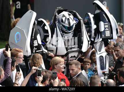 dpatop - Berlin, Germany. 18 August 2019. German Chancellor Angela Merkel with a robot and her visitors Photo: Michael Kappeler/dpa Credit: dpa picture alliance/Alamy Live News - Stock Photo
