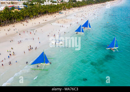 BORACAY ISLAND, PHILIPPINES - JUNE 18 2019: Aerial view of crowds gathering on Boracay Island's famous White Beach to watch the sunset. Stock Photo