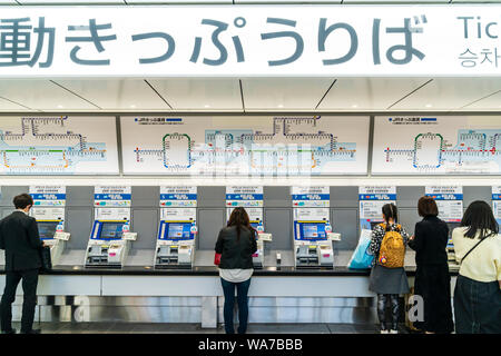Japan, Hiroshima station interior. People in line to buy tickets from row of automatic ticket machines. Overhead display with station map. - Stock Photo