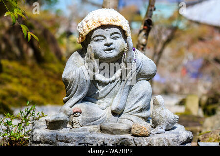 Japan, Miyajima. Daisho-in temple. Small Jizo statue of a sitting Buddhist monk in contemplation, with both hands raised as if in breakthrough moment. - Stock Photo