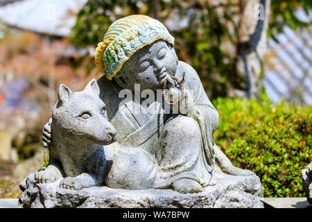 Japan, Miyajima. Daisho-in temple. Small Jizo statue of a sitting Buddhist monk in contemplation, holds a rosary in one hand and arm is around a dog. - Stock Photo