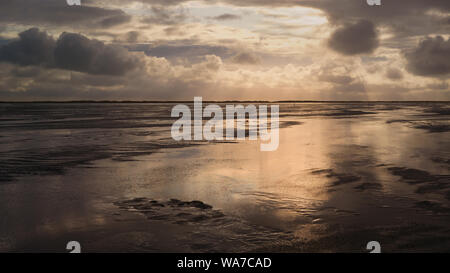 Sunset over the Wadden Sea National Park, UNESCO World Heritage Site. North Sea mud flats in epic twilight at low tide. Island of Romo, Denmark. - Stock Photo