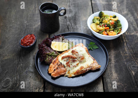 Fish and vegetables baked with tomatoes and cheese - Stock Photo