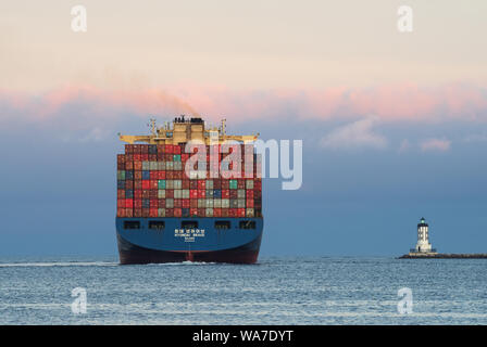 Image of a Hyundai container ship shown departing the port at dusk. - Stock Photo