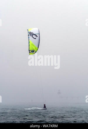 St Joseph MI USA June 1 2018; a man with a kite board enjoys being on the misty lake Michigan with fog rolling in - Stock Photo