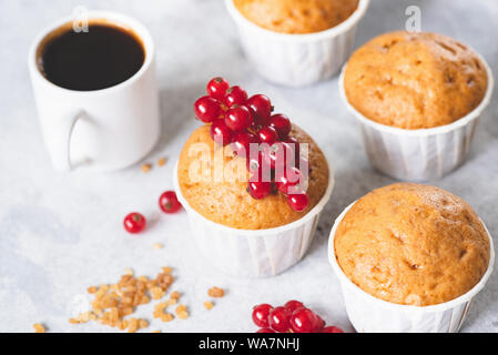 Homemade sweet vanilla muffins decorated with red berries and cup of black coffee espresso - Stock Photo