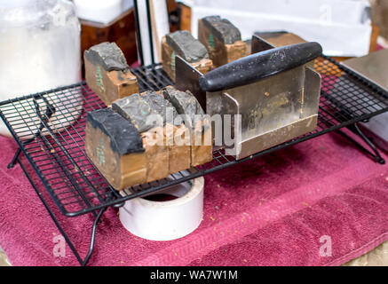 slices of gourmet soap are hand made, cut with this unique tool, and are set on a wire rack to dry out - Stock Photo