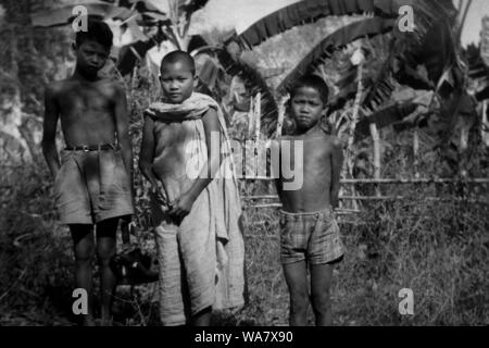 AJAXNETPHOTO. 1953-1957 (APPROX). INDO CHINA. VIETNAM. (IN-COUNTRY LOCATION UNKNOWN.) -  THREE YOUNG BOYS, ONE (CENTRE) WITH SHAVED HEAD WEARING BUDDHIST ROBE, IN A PLANTATION LANDSCAPE.PHOTO:JEAN CORRE/AJAXREF:RX7_191508_240 - Stock Photo