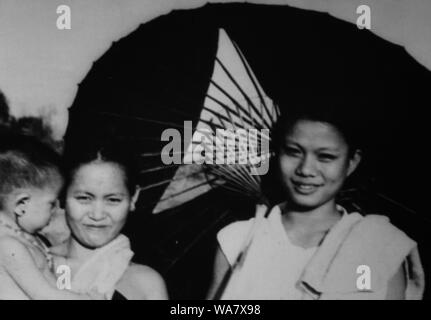AJAXNETPHOTO. 1953-1957 (APPROX). INDO CHINA. VIETNAM. (IN-COUNTRY LOCATION UNKNOWN.) - TWO WOMEN WITH A CHILD AND TRADITIONAL PARASOL. PHOTO:JEAN CORRE/AJAXREF:RX7_191508_224 - Stock Photo