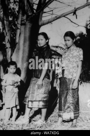 AJAXNETPHOTO. 1953-1957 (APPROX). INDO CHINA. VIETNAM. (IN-COUNTRY LOCATION UNKNOWN.) -  TWO GIRLS IN TRADITIONAL DRESS WITH SMALL CHILD POSE FOR THE CAMERA .PHOTO:JEAN CORRE/AJAXREF:RX7_191508_232 - Stock Photo